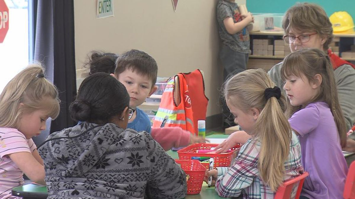 Child care workers play with children. (Credit: Alicia Naspretto, KSNB)