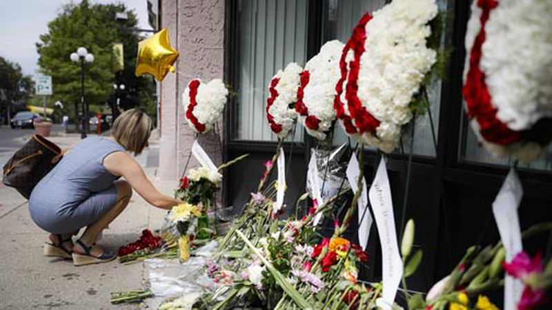 Mourners bring flowers to a makeshift memorial for the slain in the Oregon District after a...