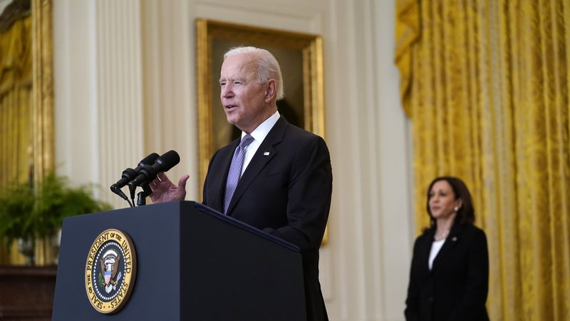 Vice President Kamala Harris listens as President Joe Biden speaks about distribution of...