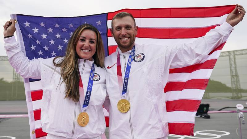 Amber English, left, and Vincent Hancock, both of the United States, celebrate taking the gold...