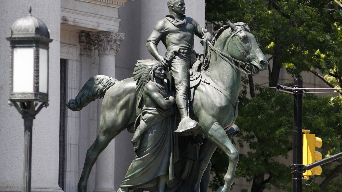 A statue of Theodore Roosevelt on horseback guided by a Native American man, and an African man sits in front of the American Museum of Natural History, Monday, June 22, 2020, in New York. An African man is depicted at Roosevelt's side on the opposite side, not visible from this angle. The statue, which was installed in1940, will be taken down after objections that it symbolizes colonial expansion and racial discrimination. Mayor Bill de Blasio said Sunday the city supports removal of the statue because it depicts Black and Indigenous people as subjugated and racially inferior. (AP Photo/Kathy Willens)