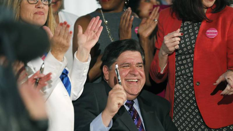 FILE - In this June 12, 2019 file photo, Illinois Gov. J.B. Pritzker signs the Reproductive...