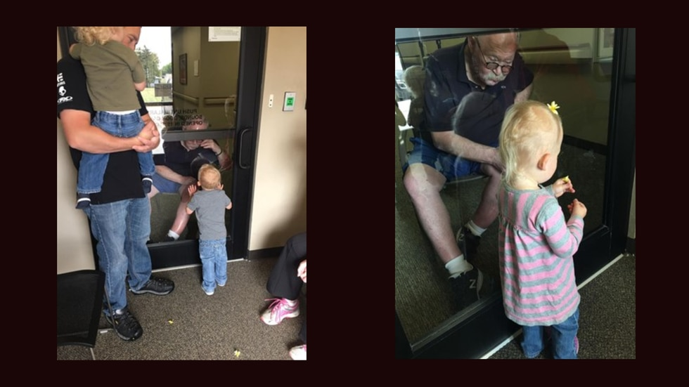 Milt Nelson visits with his grandchildren through glass windows on Sept. 12, 2020. His daughter, Chelsea Dagen, said they have not been able to touch him since the pandemic began. Complicating matters, they live in South Dakota, where cases are not improving.