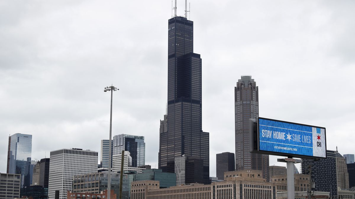 A public service message Stay Home Saves Lives is seen against the Chicago skyline Monday, March 30, 2020. The new coronavirus causes mild or moderate symptoms for most people, but for some, especially older adults and people with existing health problems, it can cause more severe illness or death.
