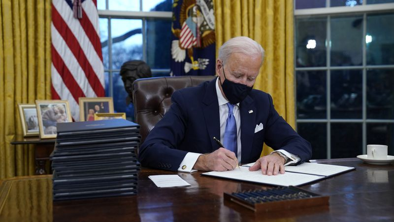 President Joe Biden signs his first executive order in the Oval Office of the White House on...
