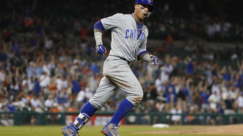 Chicago Cubs' Javier Baez reacts while rounding the base after hitting a a three-run home run...