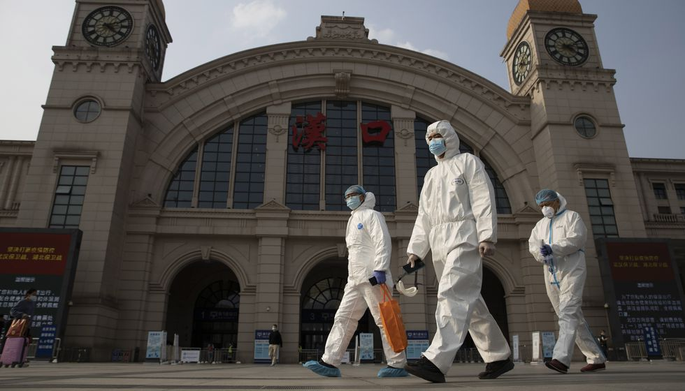 FILE - In this April 7, 2020 file photo, workers in protective suits walk past the Hankou...