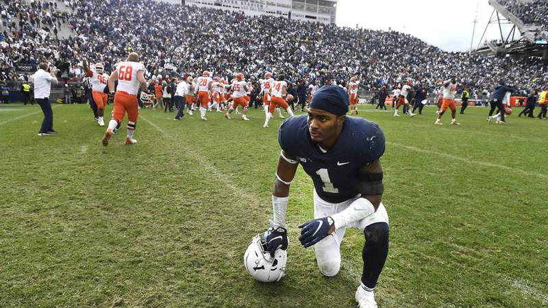 Penn State safety Jaquan Brisker (1) reacts as Illinois players celebrate their 20-18 victory...