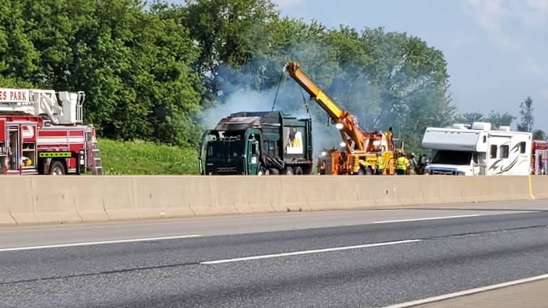 A Waste Management truck is on fire blocking two lanes in I-90 heading west near Harlem Road.
