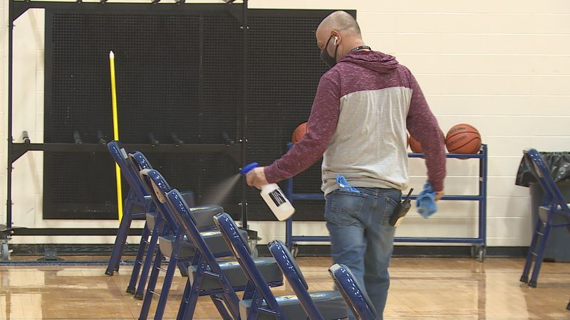 A person sanitizes the seats in between basketball games at Guilford High School. It's part of...