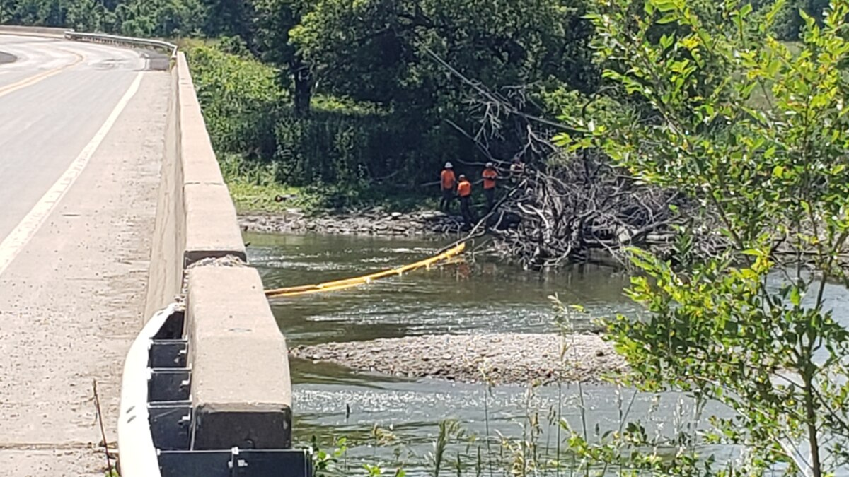 Emergency crews place protective booms in the Rock River to catch any potential runoff from the...