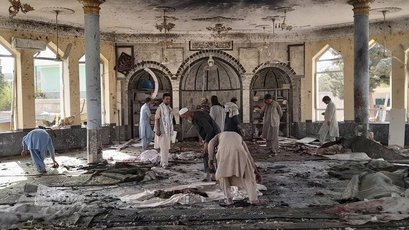 People view the damage inside of a mosque following a bombing in Kunduz, province northern...