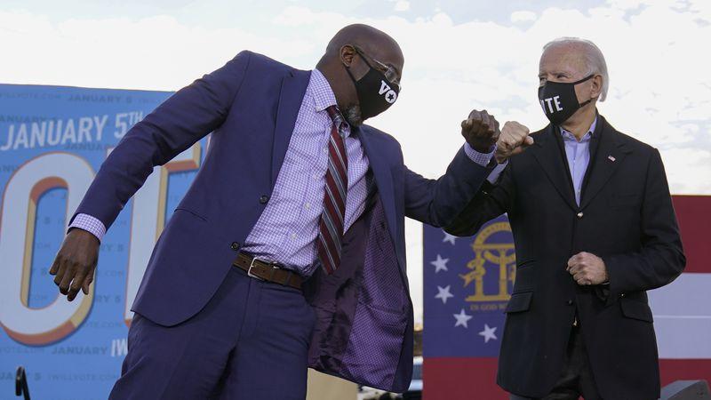 President-elect Joe Biden elbow bumps Senate candidate Raphael Warnock in Atlanta, Monday, Jan....