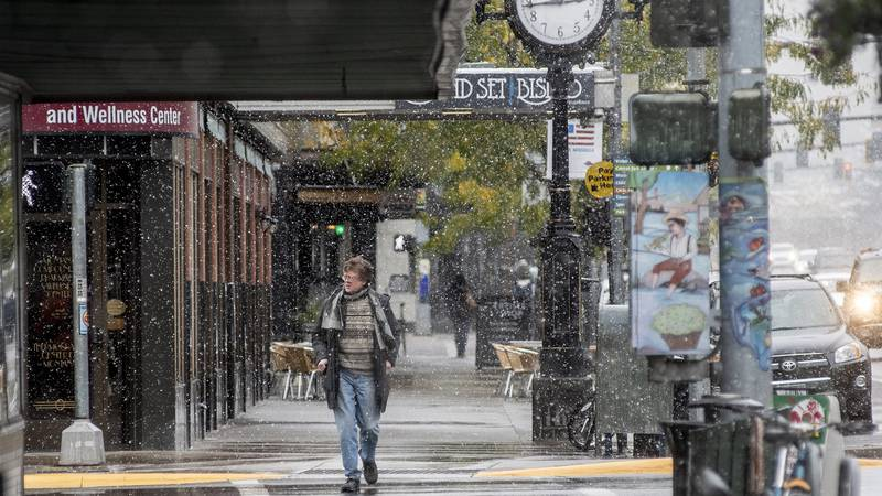 FILE - In this Sept. 29, 2019 file photo, a pedestrian crosses Front Street under snowfall in...