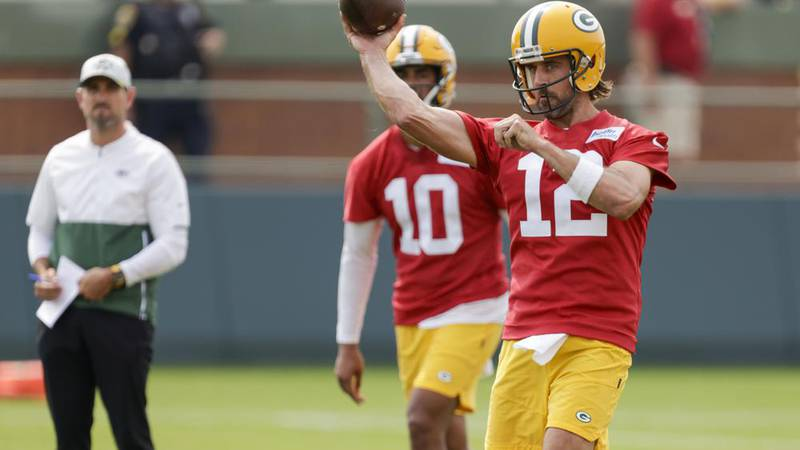 Green Bay Packers' quarterback Aaron Rodgers (12) passes while head coach Matt LaFleur and...
