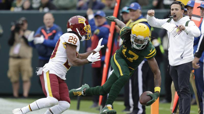 Green Bay Packers' Davante Adams is pushed out of bounds by Washington Football Team's Kendall...