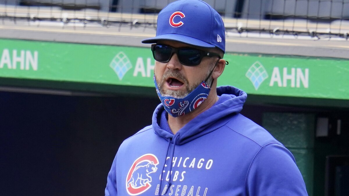 Chicago Cubs manager David Ross stands in the dugout during a baseball game against the...