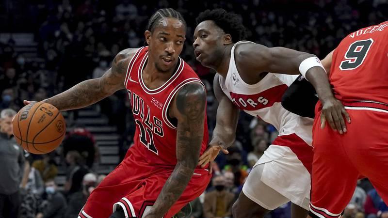 Chicago Bulls forward DeMar DeRozan (11) moves the ball around Toronto Raptors forward OG...