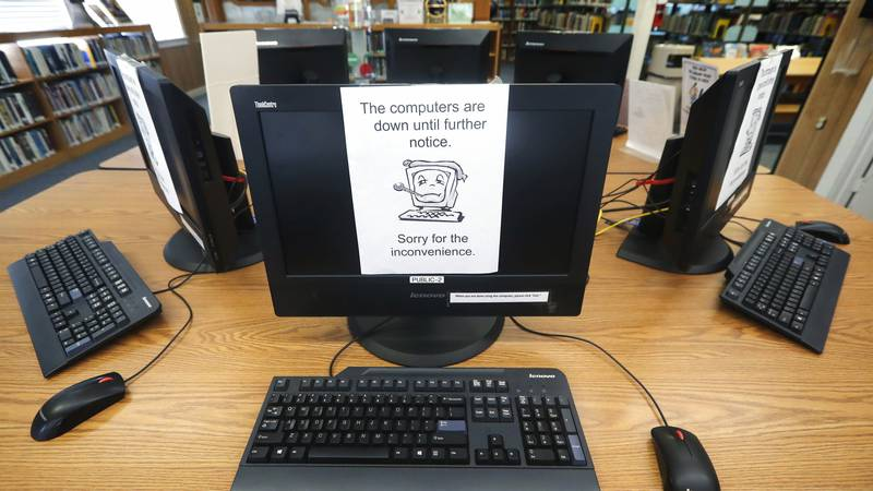 FILE - In this Aug. 22, 2019, file photo, signs on a bank of computers tell visitors that the...
