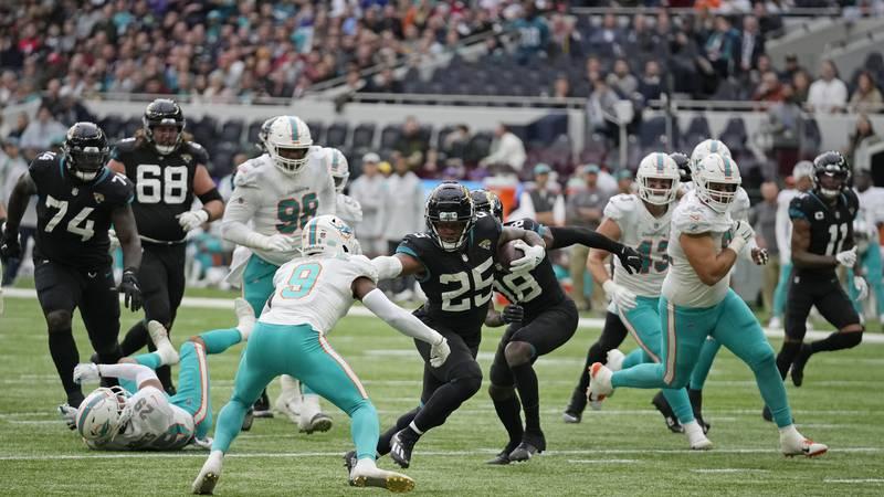 Jacksonville Jaguars running back James Robinson (25), center, makes yards on a drive that...