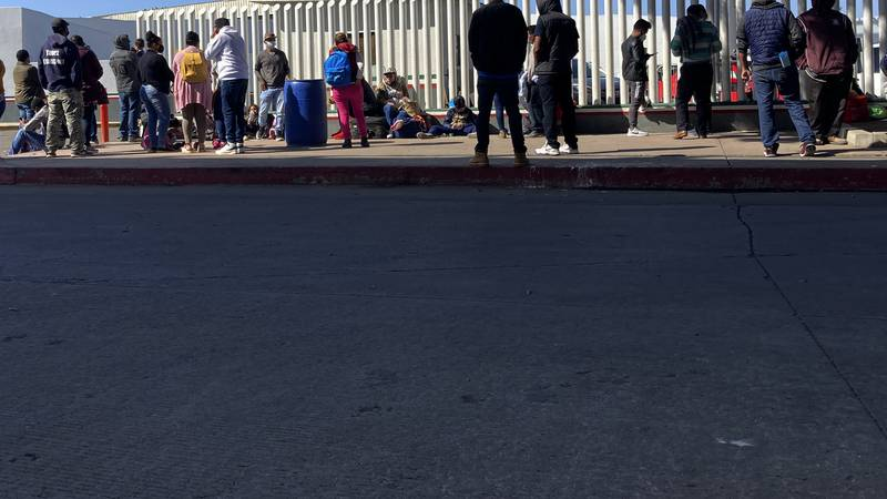 Migrants waiting to cross into the United States wait for news at the border crossing...
