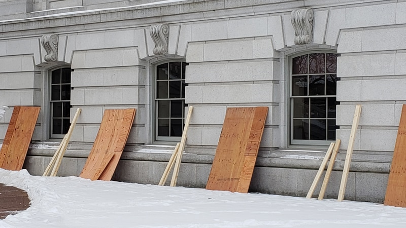 Crews set up to board the first floor windows of the state capitol building in Madison,...