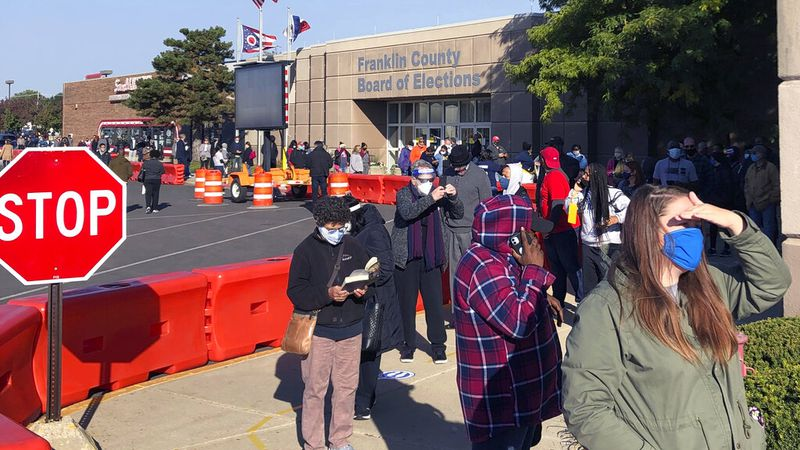 Ohio voters wait in line at the Franklin County Board of Elections on the first day of early...
