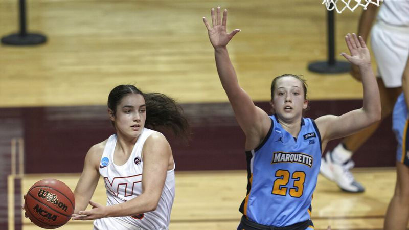 Virginia Tech's Georgia Amoore, left, looks to pass the ball as Marquette's Jordan King (23)...