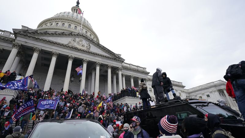 Trump supporters stand on top of a police vehicle, Wednesday, Jan. 6, 2021, at the Capitol in...