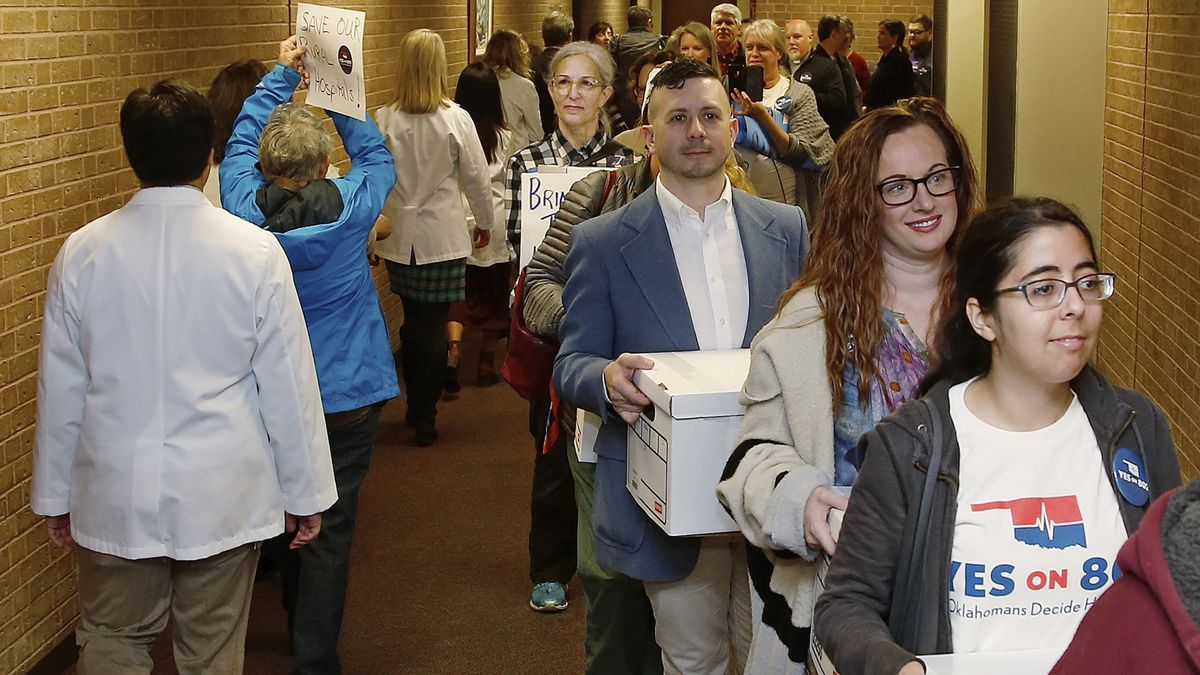 In this Oct. 24, 2019 file photo, supporters of Yes on 802 Oklahomans Decide Healthcare, calling for Medicaid expansion to be put on the ballot, carry boxes of petitions into the office of the Oklahoma Secretary of State in Oklahoma City.