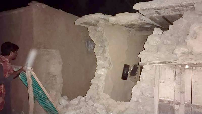 A local resident looks his damaged house following a severe earthquake hit the area, in Harnai,...