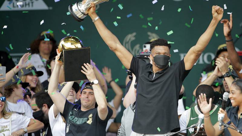 Milwaukee Bucks' Giannis Antetokounmpo holds up the Finals MVP trophy as confetti falls during...